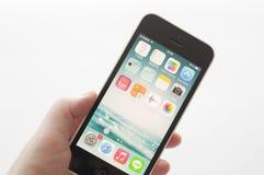 IPhone de Apple em uma mão fêmea Fotografia de Stock Royalty Free
