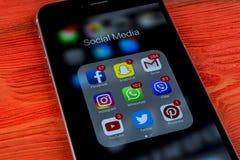 IPhone 7 de Apple en la tabla de madera con los iconos del medios facebook social, instagram, gorjeo, uso del snapchat en la pant Fotografía de archivo libre de regalías