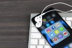 IPhone 7 de Apple en la tabla de madera con los iconos del medios facebook social, instagram, gorjeo, uso del snapchat en la pant Fotos de archivo libres de regalías