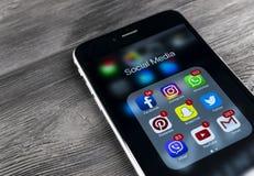 IPhone 7 de Apple en la tabla de madera con los iconos del medios facebook social, instagram, gorjeo, uso del snapchat en la pant Fotos de archivo