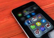 IPhone 7 de Apple en la tabla de madera con los iconos del medios facebook social, instagram, gorjeo, uso del snapchat en la pant Imágenes de archivo libres de regalías