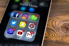 IPhone 7 de Apple en la tabla de madera con los iconos del medios facebook social, instagram, gorjeo, uso del snapchat en la pant Imagenes de archivo