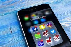 IPhone 7 de Apple en la tabla de madera con los iconos del medios facebook social, instagram, gorjeo, uso del snapchat en la pant Foto de archivo libre de regalías