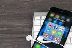 IPhone 7 de Apple en la tabla de madera con los iconos del medios facebook social, instagram, gorjeo, uso del snapchat en la pant Imagen de archivo libre de regalías