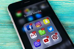 IPhone de Apple 7 más en la tabla de madera azul con los iconos del medios facebook social, instagram, gorjeo, uso del snapchat e Foto de archivo libre de regalías