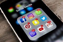 IPhone de Apple 7 más en la tabla de madera negra con los iconos del medios facebook social, instagram, gorjeo, uso del snapchat  Imagen de archivo libre de regalías
