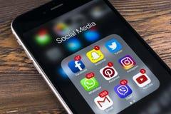 IPhone 7 de Apple na tabela de madeira com ícones do facebook social dos meios, instagram, gorjeio, aplicação do snapchat na tela Imagem de Stock