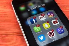 IPhone 7 de Apple na tabela de madeira com ícones do facebook social dos meios, instagram, gorjeio, aplicação do snapchat na tela Fotos de Stock