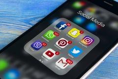 IPhone 7 de Apple na tabela de madeira com ícones do facebook social dos meios, instagram, gorjeio, aplicação do snapchat na tela Foto de Stock
