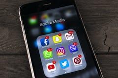 IPhone 7 de Apple na tabela de madeira preta com ícones do facebook social dos meios, instagram, gorjeio, aplicação do snapchat n Fotos de Stock Royalty Free