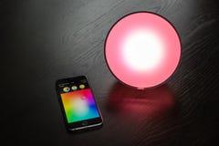 IPhone de Apple que está sendo usado para controlar uma luz home esperta de Philips Hue imagens de stock