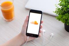 IPhone 6 della tenuta della donna con SoundCloud sullo schermo Fotografia Stock