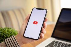 IPhone X della tenuta della donna con il flusso continuo di video servizio YouTub di media immagini stock libere da diritti