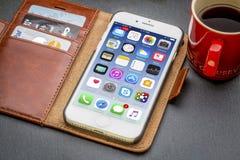 IPhone 7 in der ledernen Geldbörse mit Kaffee Stockfotos