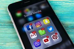 IPhone di Apple 7 più sulla tavola di legno blu con le icone del facebook sociale di media, instagram, cinguettio, applicazione d Fotografia Stock Libera da Diritti