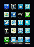 Iphone display with social network apps. Muenster, Germany, April 16, 2011: Image of the iphone touch screen. Display shows a collection of useful apps with blue Royalty Free Stock Photos