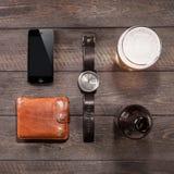 Iphone e della birra degli orologi vicino su di legno Fotografia Stock