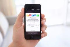 IPhone 5 en la mano masculina con la libreta de banco en la pantalla Imágenes de archivo libres de regalías