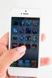 IPhone 5 en una mano aislada en blanco imagen de archivo