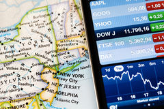 Iphone with financial application on map of North America, Stock Photography