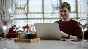 Απόμακρη άποψη μιας νέας συνεδρίασης επιχειρηματιών σε έναν πίνακα σε έναν καφέ χρησιμοποιώντας το iphone και γελώντας, που προσέ απόθεμα βίντεο