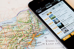 IPhone with hotel booking application on a map of USA Royalty Free Stock Photo