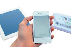 Мужская рука держа белый прибор Яблока Iphone выше и прибор Яблока Ipad и случай Iphone на предпосылке Стоковые Фото