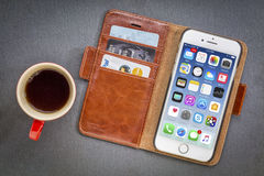 IPhone 7 in leather wallet with coffee Stock Image
