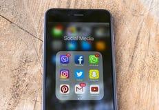 Iphone 6 más con los iconos de medios sociales en la pantalla en la tabla de madera natural Smartphone del estilo de vida de Smar Imagen de archivo libre de regalías