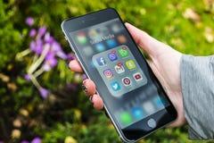 Iphone 6 más con los iconos de medios sociales en manos de la muchacha Smartphone del estilo de vida de Smartphone Comenzar los m Fotos de archivo libres de regalías