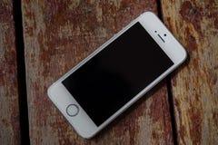 IPhone móvil blanco en la madera de Brown Fotos de archivo libres de regalías