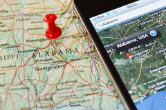 Iphone met navigatietoepassing op kaart van Alabama Stock Fotografie