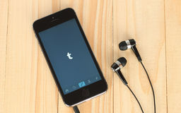 IPhone met Tumblr logotype op het zijn scherm en hoofdtelefoons Royalty-vrije Stock Afbeelding