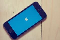 IPhone mit Twitter-APP auf hölzernem Hintergrund Lizenzfreie Stockfotos