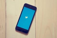 IPhone mit Twitter-APP auf hölzernem Hintergrund Stockfotografie