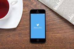 IPhone mit Twitter auf dem Schirm, der auf einem Holztisch in liegt Stockbilder