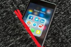 IPhone negro de Apple con los iconos de medios sociales: instagram, youtube, reddit, facebook, gorjeo, snapchat, usos del whatsap imagen de archivo libre de regalías