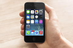 Iphone with new ios 7. Hand holding a iPhone 4s with new ios 7 operating system Royalty Free Stock Images