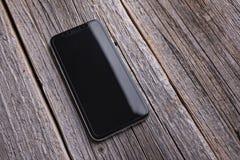 IPhone novo X 10 em um fundo de madeira, tiro do estúdio foto de stock