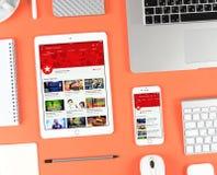 Iphone och ipad över röd bakgrund som visar Youtube app Royaltyfri Foto