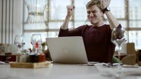 Далекий взгляд молодого бизнесмена сидя на таблице в кафе используя iphone и смеясь, наблюдая прохожих акции видеоматериалы