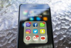 Iphone 6 plus avec des icônes de media social sur l'écran sur la table en bois verte Smartphone de style de vie de Smartphone Com Image libre de droits