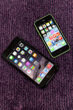 iphone 6 plus home screen full of icons with an iphone 5c side by side Stock Photo