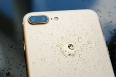 IPhone 7 plus vattentätt med regn tappar på bakre glass backgroud Royaltyfri Bild