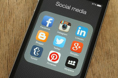 IPhone with popular social media icons on its screen. KIEV, UKRAINE - JUNE 23, 2015: iPhone with popular social media icons on its screen on wooden background vector illustration