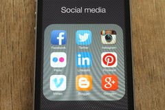 IPhone with popular social media icons on its screen on wooden background Royalty Free Stock Photos