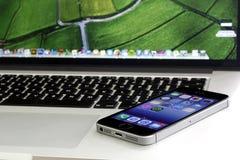 IPhone 5s που βρίσκεται στον αμφιβληστροειδή macbook υπέρ Στοκ Φωτογραφία