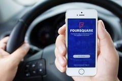 IPhone 5S app Foursquare in handen van de bestuurdersauto Stock Afbeeldingen