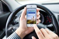IPhone 5S app TripAdvisor en las manos del coche del conductor Foto de archivo