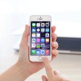 IPhone 5S com IOS 8 em uma mão no fundo de MacBook Foto de Stock Royalty Free